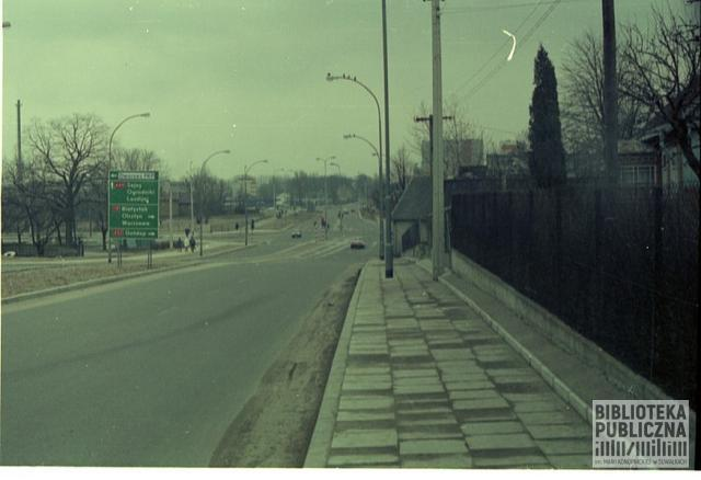 Suwałki. Fragment ulicy Dwernickiego, widok na skrzyżowanie ulic Utrata, Dwernickiego, Kolejowa. Po prawej stronie istniejące jeszcze domy mieszkalne, po lewej teren zielony, który został z czasem zagospodarowany. Obecnie znajduje się tam skwer z roślinną figurą przedstawiającą pawia. Prawdopodobnie lata 90. XX w.