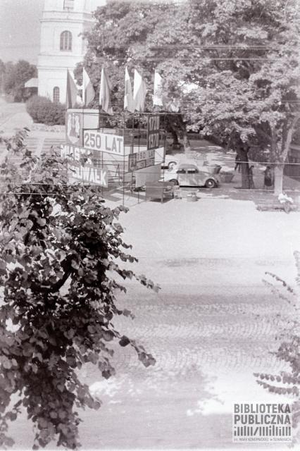 Na zdjęciu widoczny parking przy obecnym Parku Konstytucji 3 Maja. W oddali widać fragment budynku kościoła pw. Najświętszego Serca Pana Jezusa. Zdjęcie wykonane na początku l. 70. XX w.