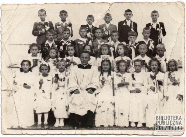 Pamiątkowe zdjęcie z pierwszej Komunii Świętej rozmówcy, w parafii św. Aleksandra w Suwałkach. W środku ksiądz Domalewski.