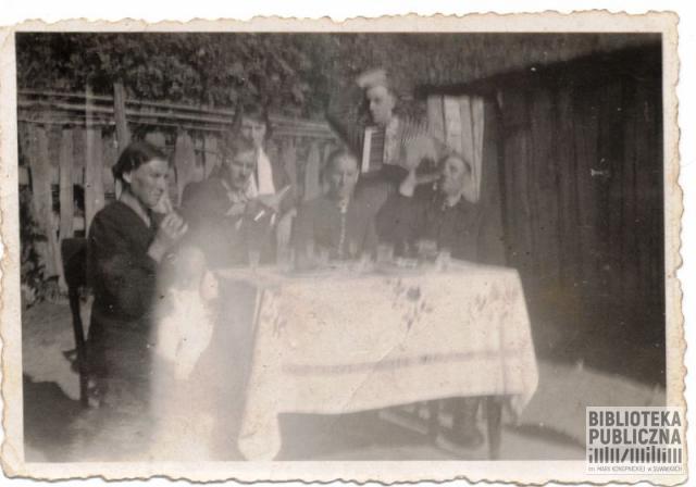 Spotkanie rodzinno-sąsiedzkie w latach 40. XX wieku. Na zdjęciu (prawdopodobnie) dziadek rozmówcy – pierwszy z prawej strony, i babka – pierwsza z lewej. Na harmonii gra prawdopodobnie ojca brat Lucjan, członek rodzinnego zespołu grającego na zabawach.