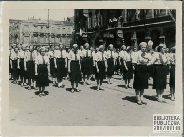 """Defilada chóru """"Suwalszczyzna"""" w Warszawie. Krawaty dziewcząt pierwszego rzędu tworzyły napis """"Suwałki"""" (widoczny fragment)"""